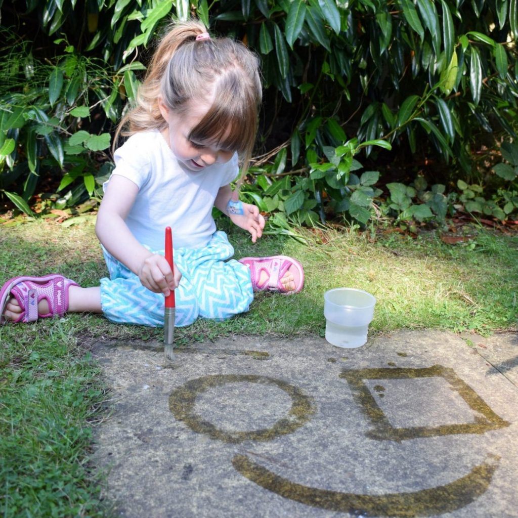 young girl sat in the garden paining with water and paintbrushes onto the paving stones