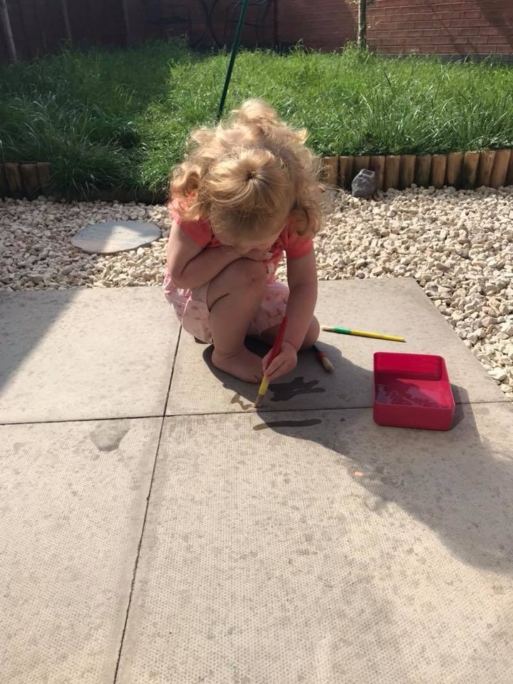 little girl paining on the paving stones with water and paintbrushes