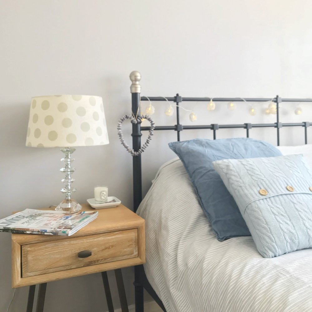 "black iron bed with blue and grey bedding and cushions - oak nightstand with laura ashley spotty lamp - diptyque candle in mimosa scent. Text overlay saying ""how to create the perfect guest room"""