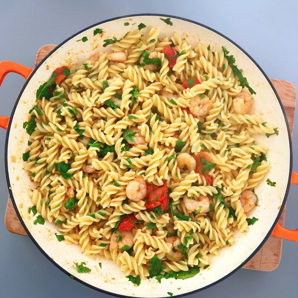 enamel pan filled with pasta with prawns, rocket and baby plum tomatoes.