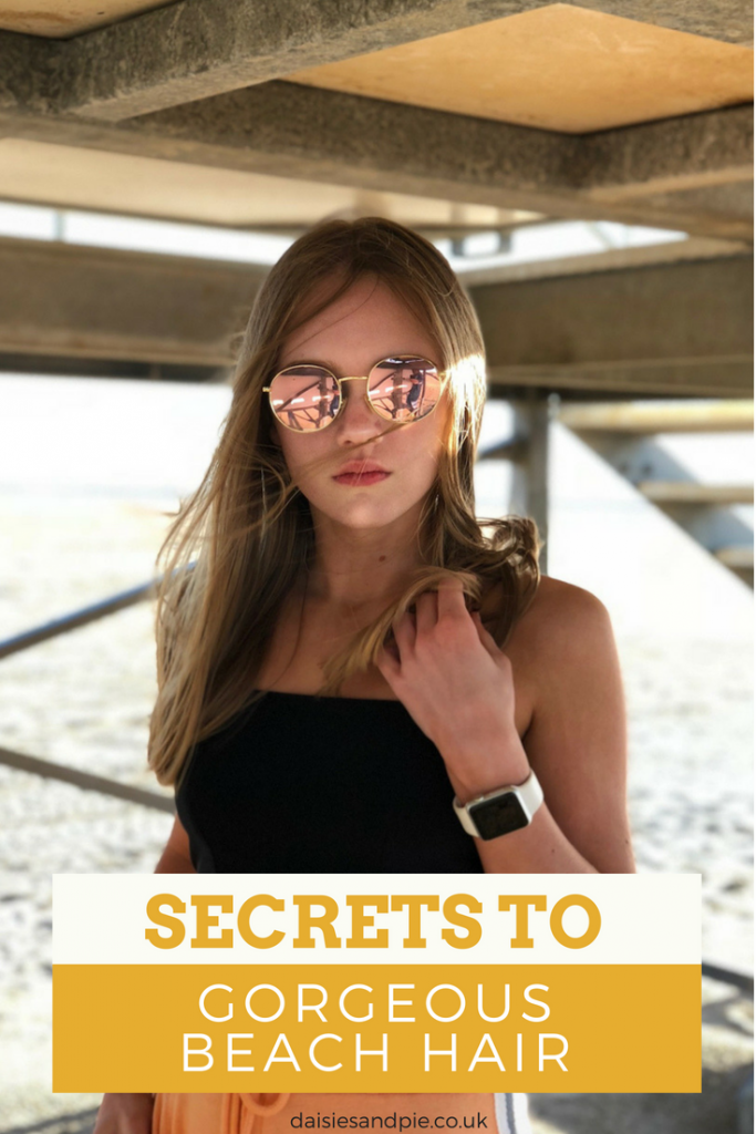 "blonde teenage girl under pier wearing black bandeaux top and orange joggers with circle metallic sunglasses. Text overlay saying ""secrets to gorgeous beach hair"""