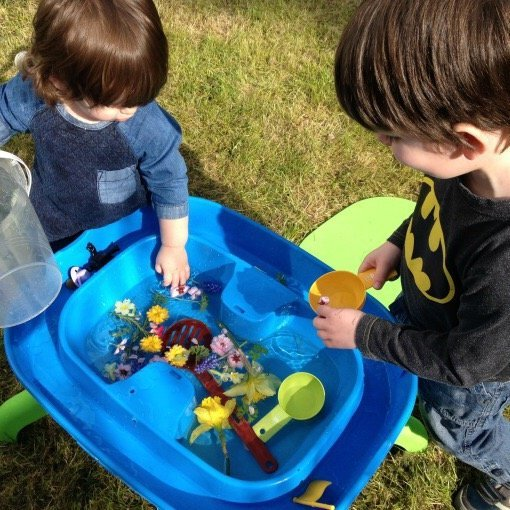 plastic tray filled with water and flowers with a little boy and girl playing