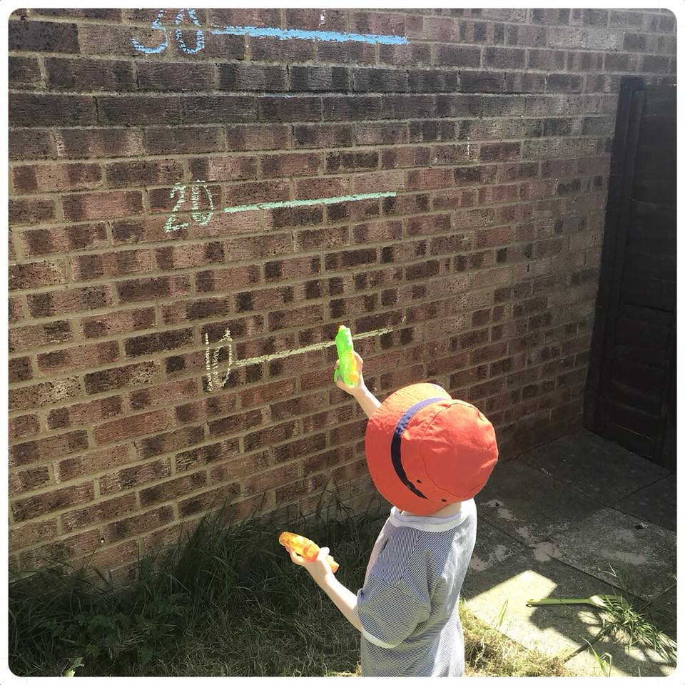small boy in the garden shooting water pistol at target shots on a brick wall