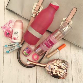 pale grey bag with pink straps wit bag contents laid alongside - zingo bottle, soft and gentle deodorant, swish toothpaste, sanitary towels, lipgloss, bobbles, hand sanitiser, concealer, body spray, tangle angel hairbrush.