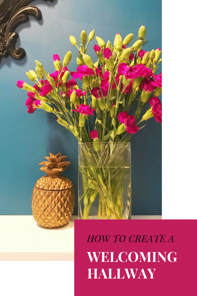 "teal walls with vase of magenta carnations and gold pineapple next to vase. Text overlay saying ""how to create a welcoming hallway"""