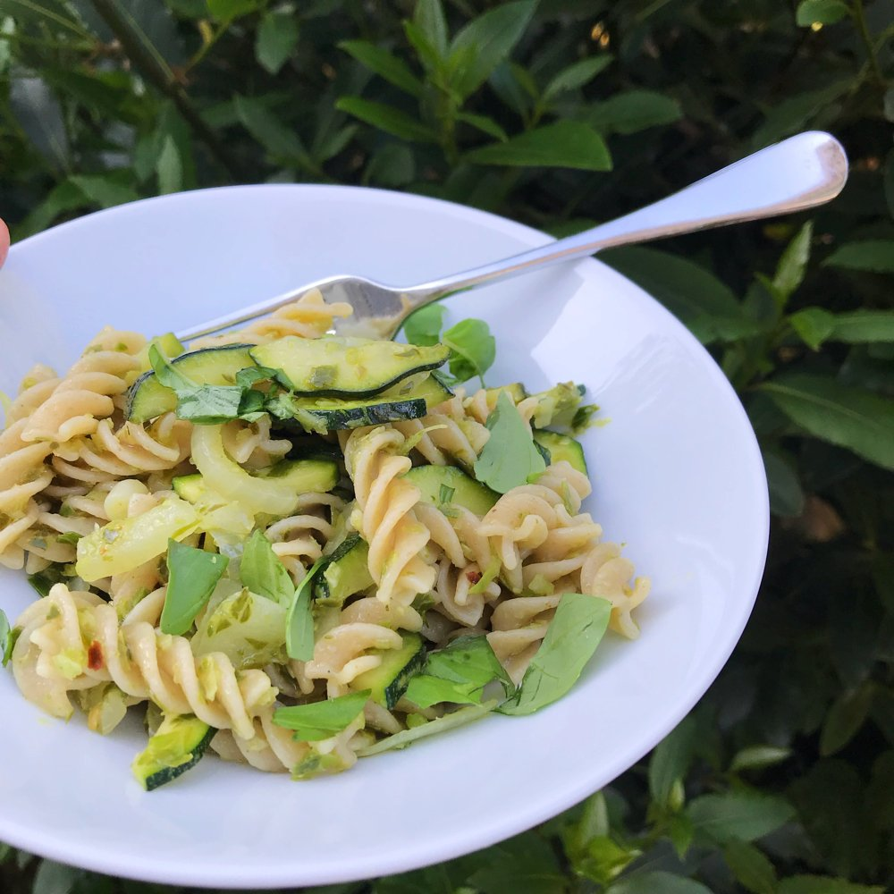 white bowl filled with wholegrain pasta tossed together with garlicky chilli spiked greens.