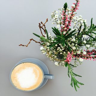 jam jar filled with summery flowers and herbs alongside a cup of real coffee.
