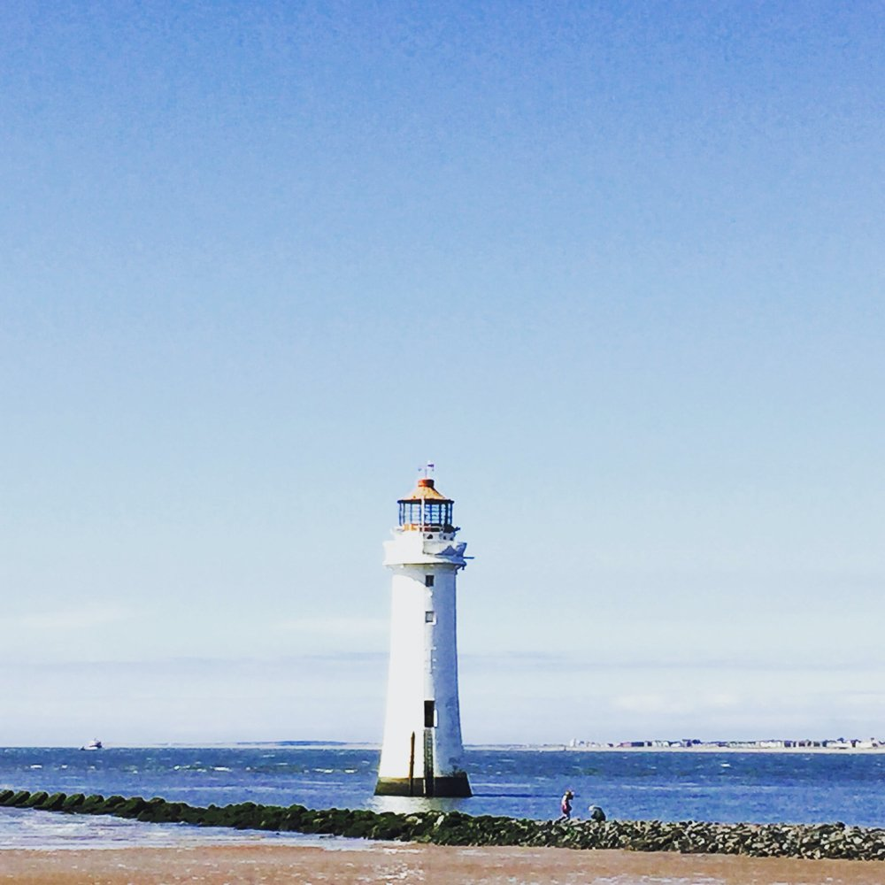 lighthouse with brilliant blue sky and sea in the background