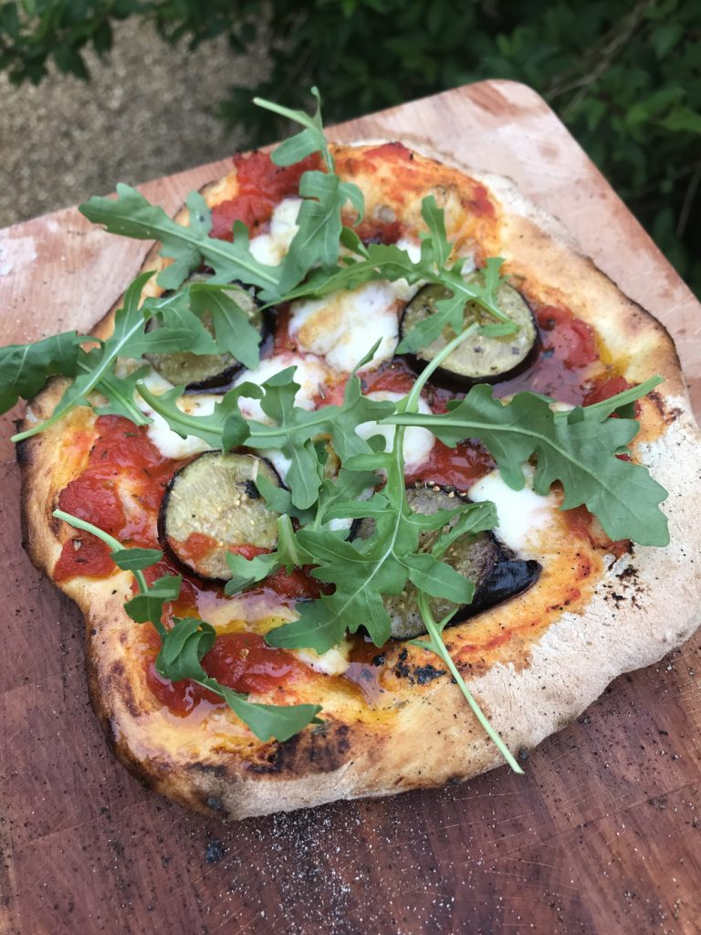 wood fired pizza topped with figs, goats cheese and rocket leaves