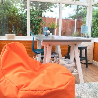 conservatory as a home office with grey table, orange beanbag chair, pale blue shaggy rug, orange painted bricks