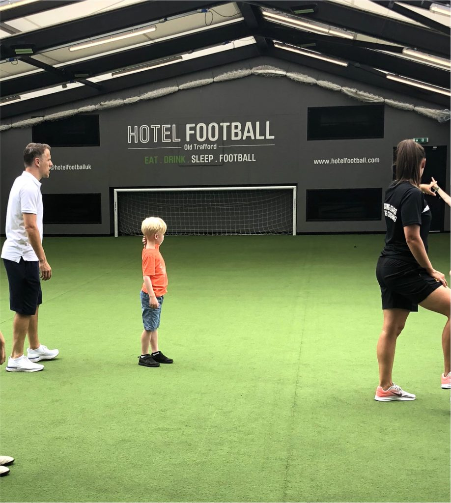 boy playing football with Phil Neville at the Summer Football Camp on the roof top pitch at Hotel Football Old Trafford