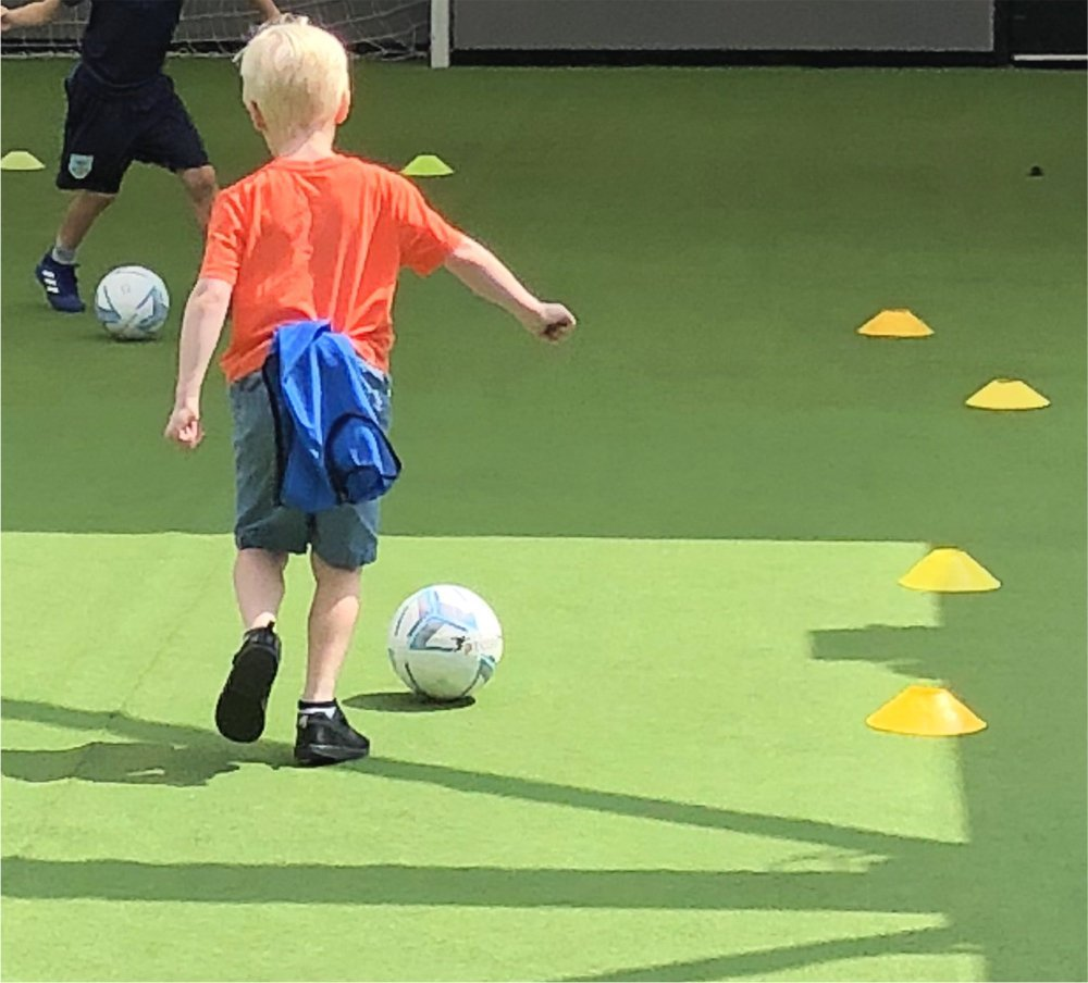 boy playing football at the Summer Football Camp on the roof top pitch at Hotel Football Old Trafford