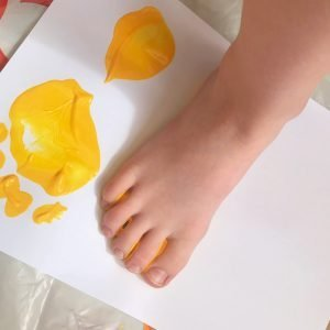 small child making painted footprints with yellow paint