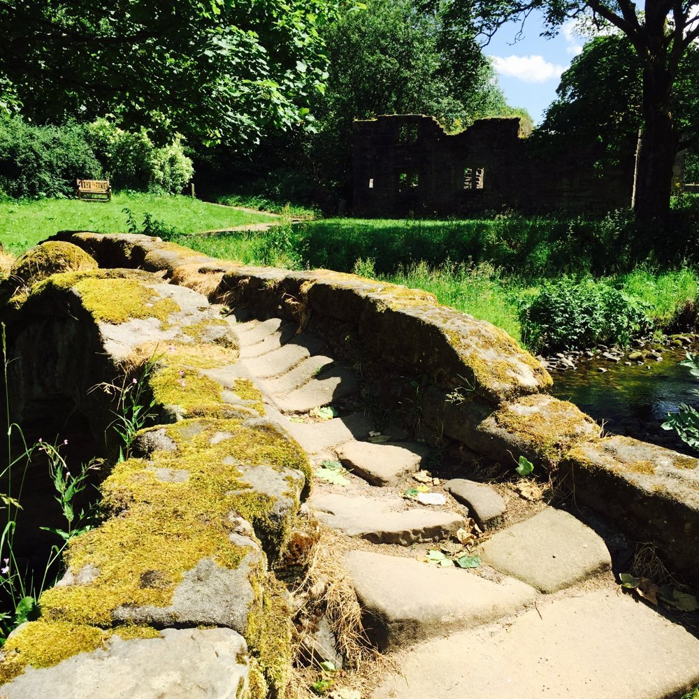 The ancient stone bridge over the river at Wycollar wit Wycollar hall ruins in the background