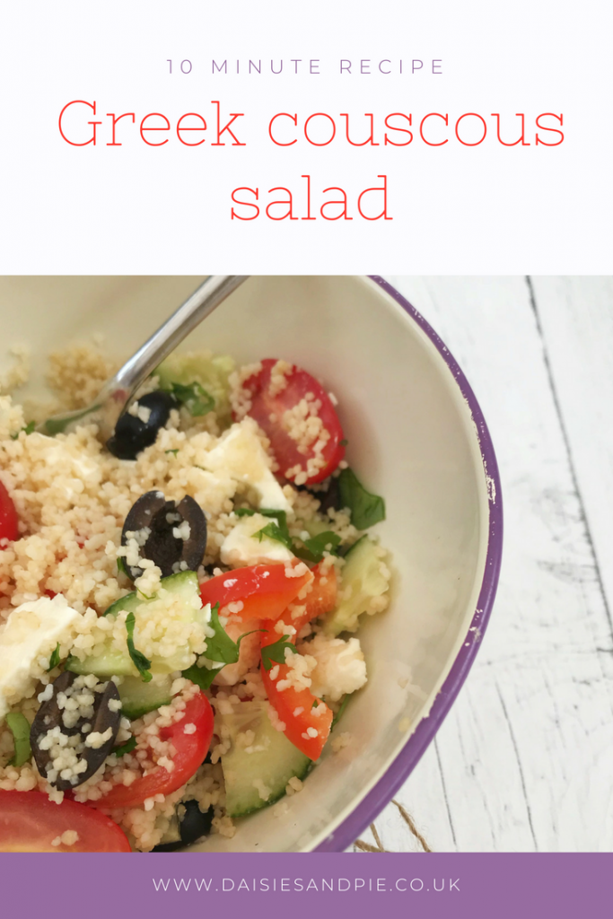 "enamel bowl filled with homemade Greek salad couscous with olives, cucumber, tomatoes, red peppers and black olives, scattered with chopped basil and flat leaf parsley. Text overlay ""10 minute Greek couscous salad"""