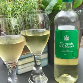 Marques de Caceres white wine with 2 glasses poured - thyme growing in the background