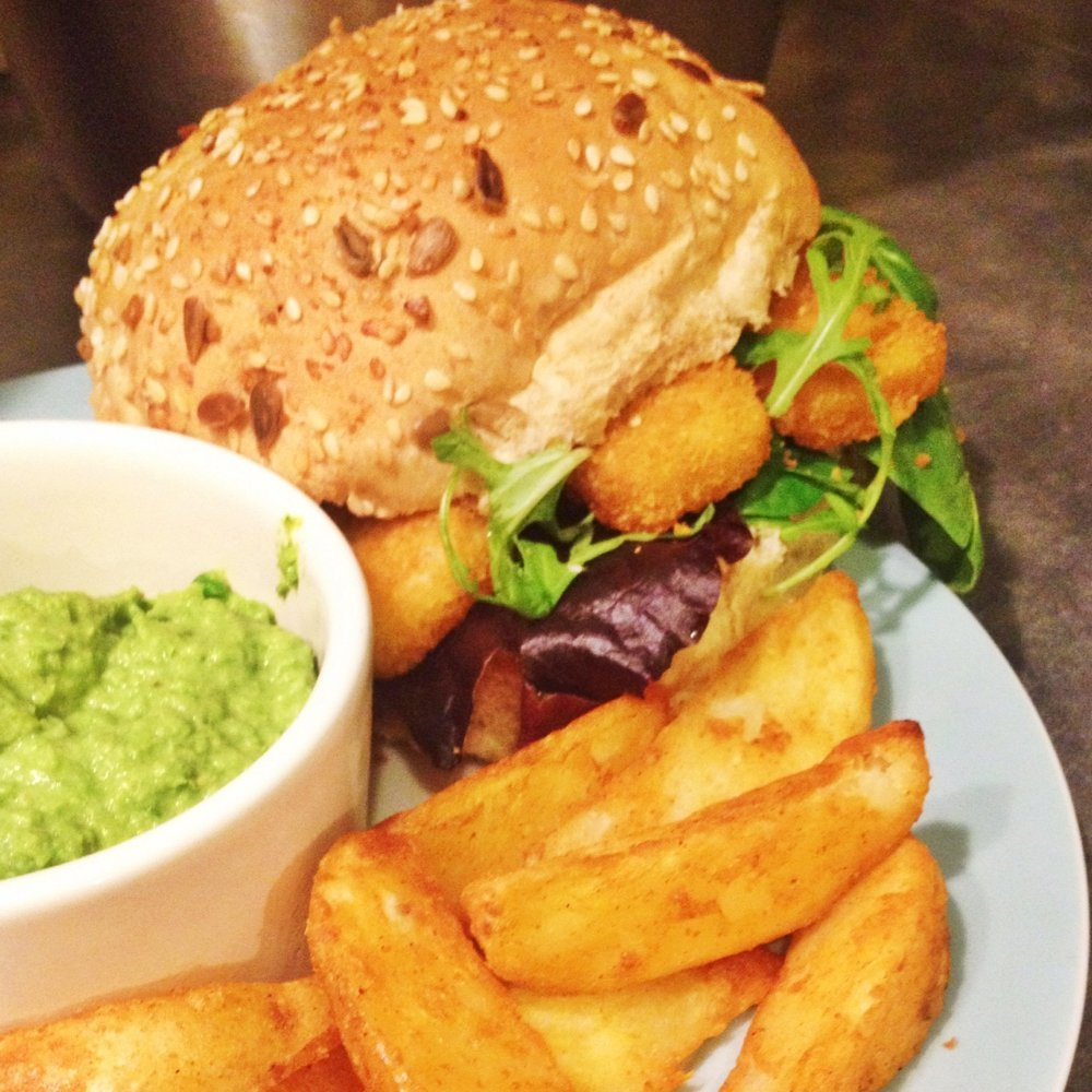 fish fingers on toasted roll with rocket salad, alongside portion of potato wedges and homemade pesto pea dip