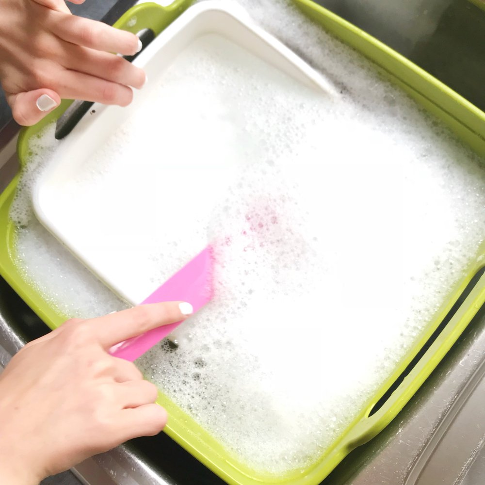 josephjoseph washing up bowl filled with soapy water and a glide dish brush being used to clean an enamel tray