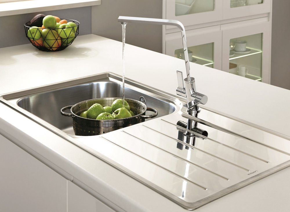 sink on island unit with colander full of apples being rinsed under the tap