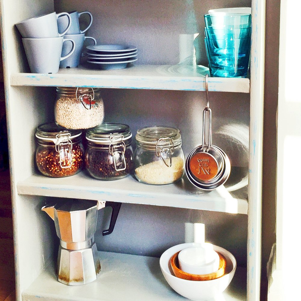 grey painted vintage shelf unit with bowls and cups and a coffee pot stored on it.