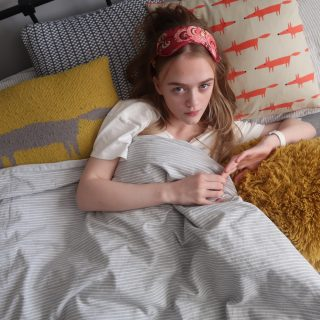 teenage girl surrounded by loads of cushions and covers