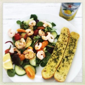 plateful of homemade spicy prawn salad served with spicy dressing and ciabatta slices - can of limoata pellegrino to the side.