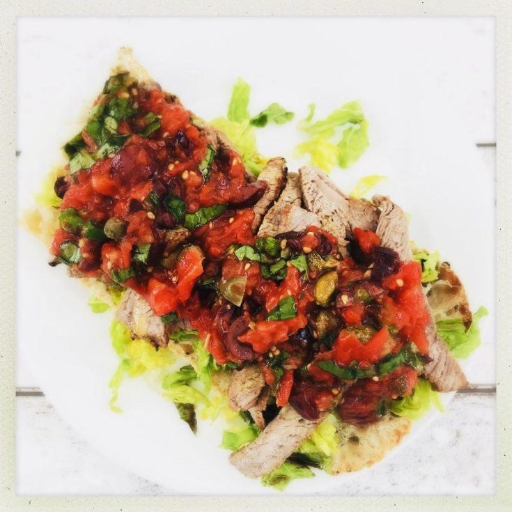 sirloin steak ciabatta sandwich topped with Italian roast tomato salsa