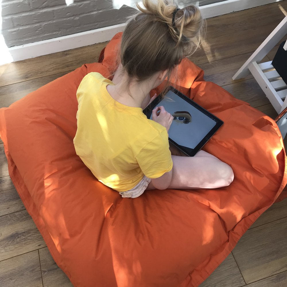 girl sat on an orange bean bag working on the iPad