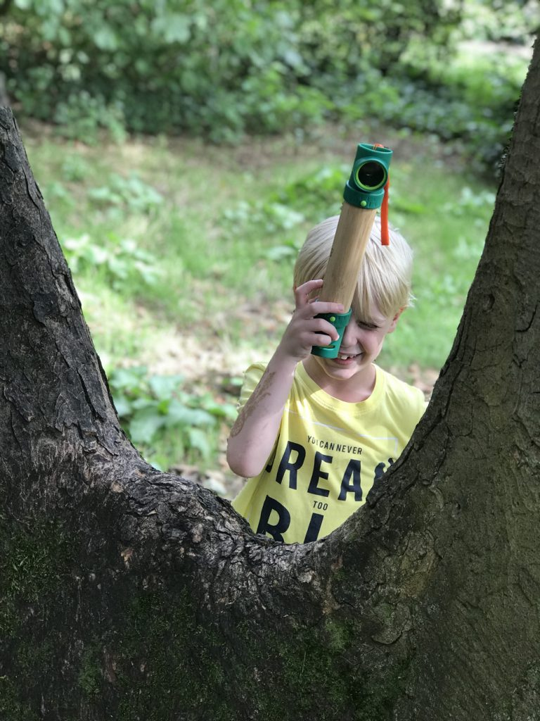blonde boy looking through a Hape periscope to see over a tree trunk