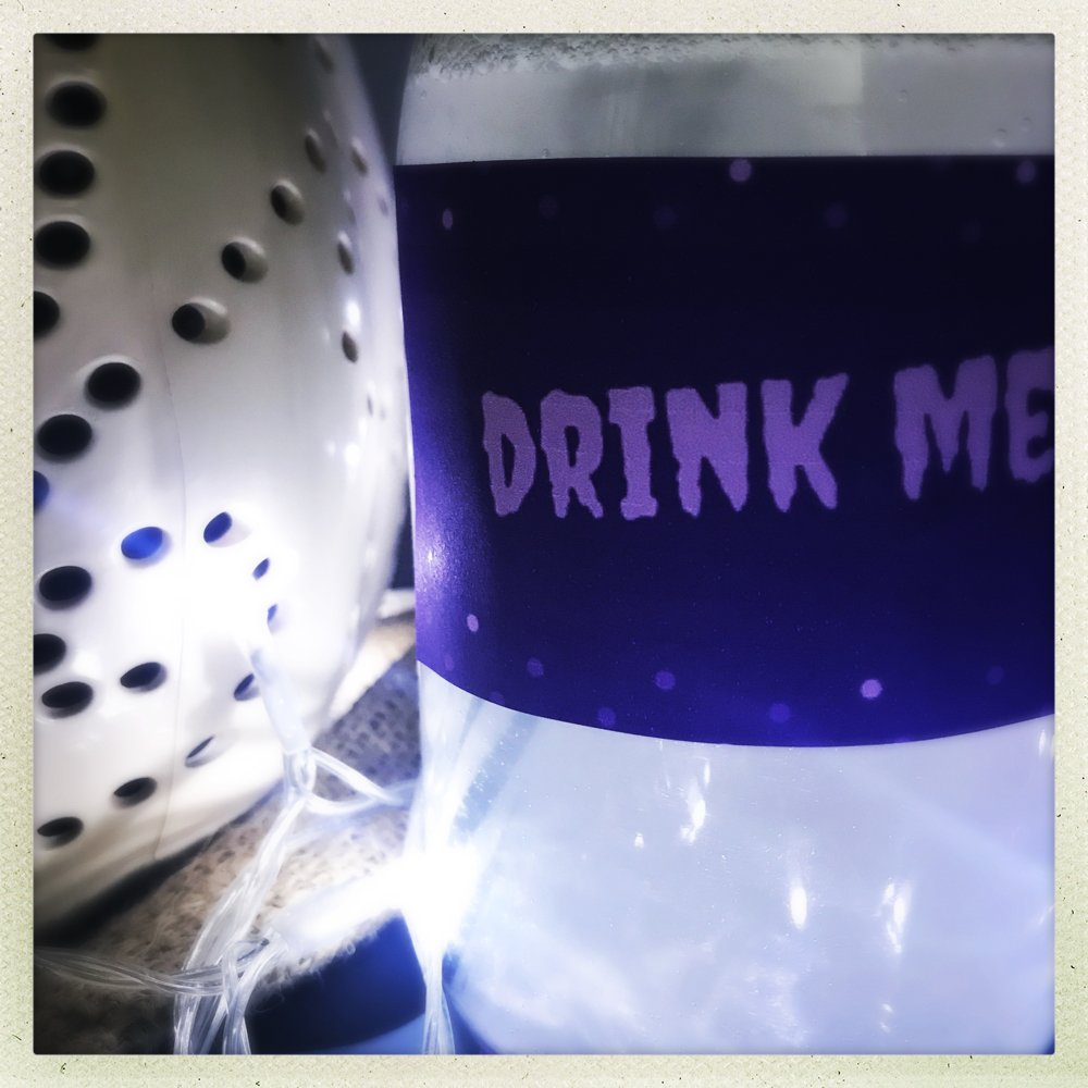 bottle of silver Halloween mocktail drink with label on saying Drink Me, white pumpkin in background.