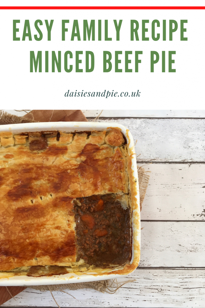 "minced beef and onion pie freshly baked pulled out of the oven  with a slice cut from the corner. Text ""easy family recipe - minced beef pie - daisiesandpie.co.uk"""