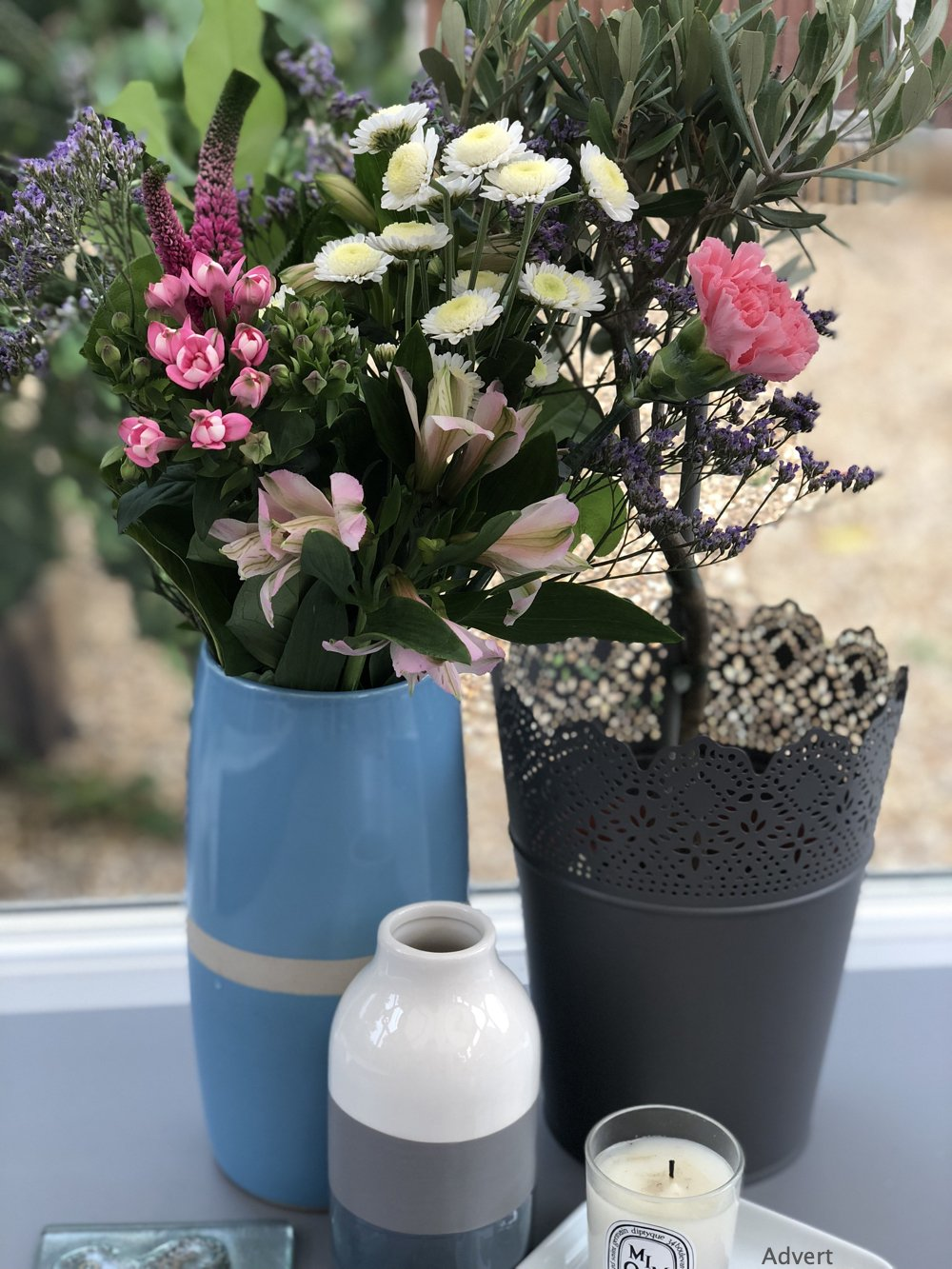 Bloom Magic flower bouquet wit roses, stock, herbs and freesia in a blue vase next to an olive tree