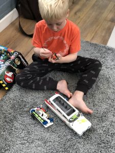 small boy playing with Playmobil Ghostbusters car