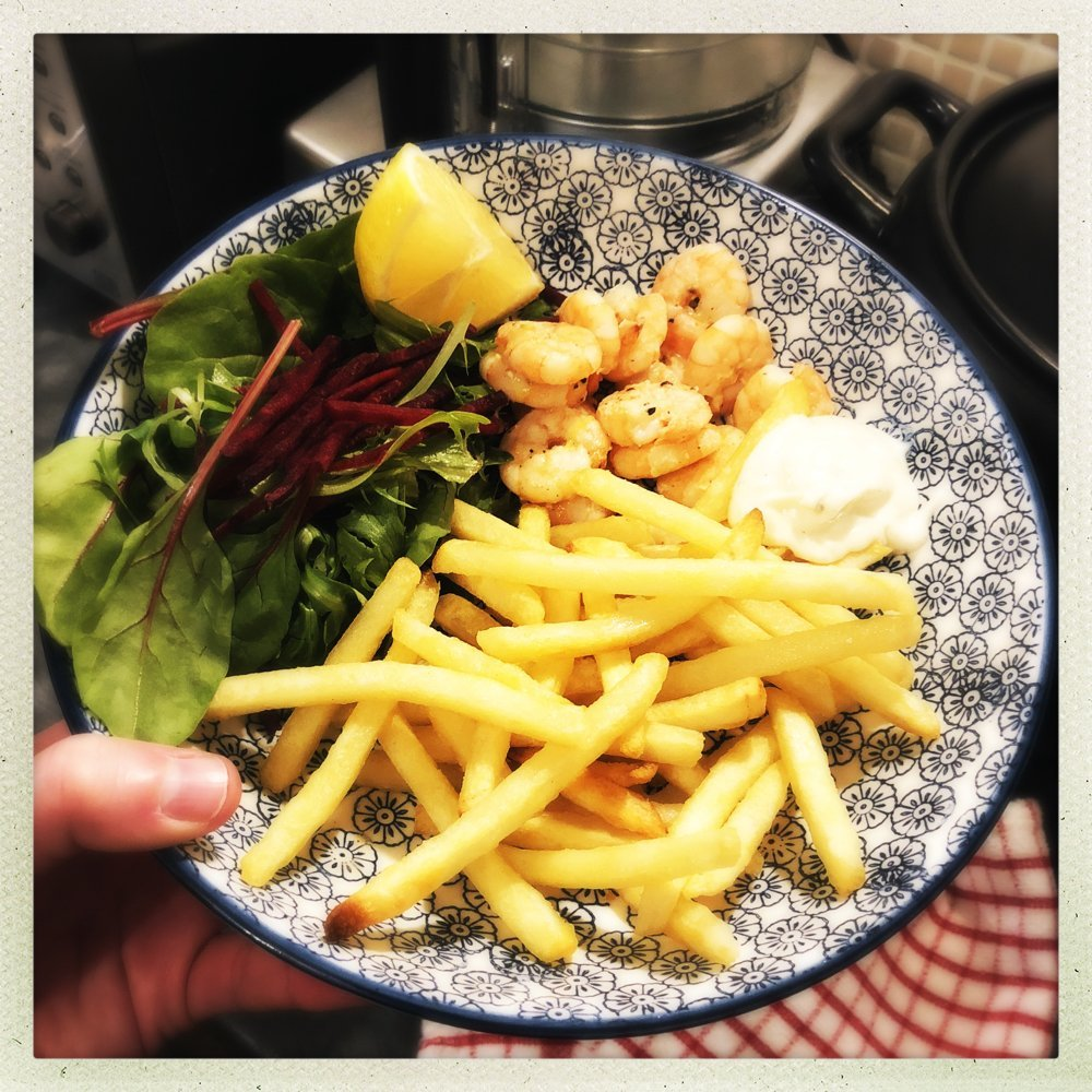 blue and white print bowl filled with homemade spicy prawns with french fries, garlic mayonnaise dip and a bistro salad.