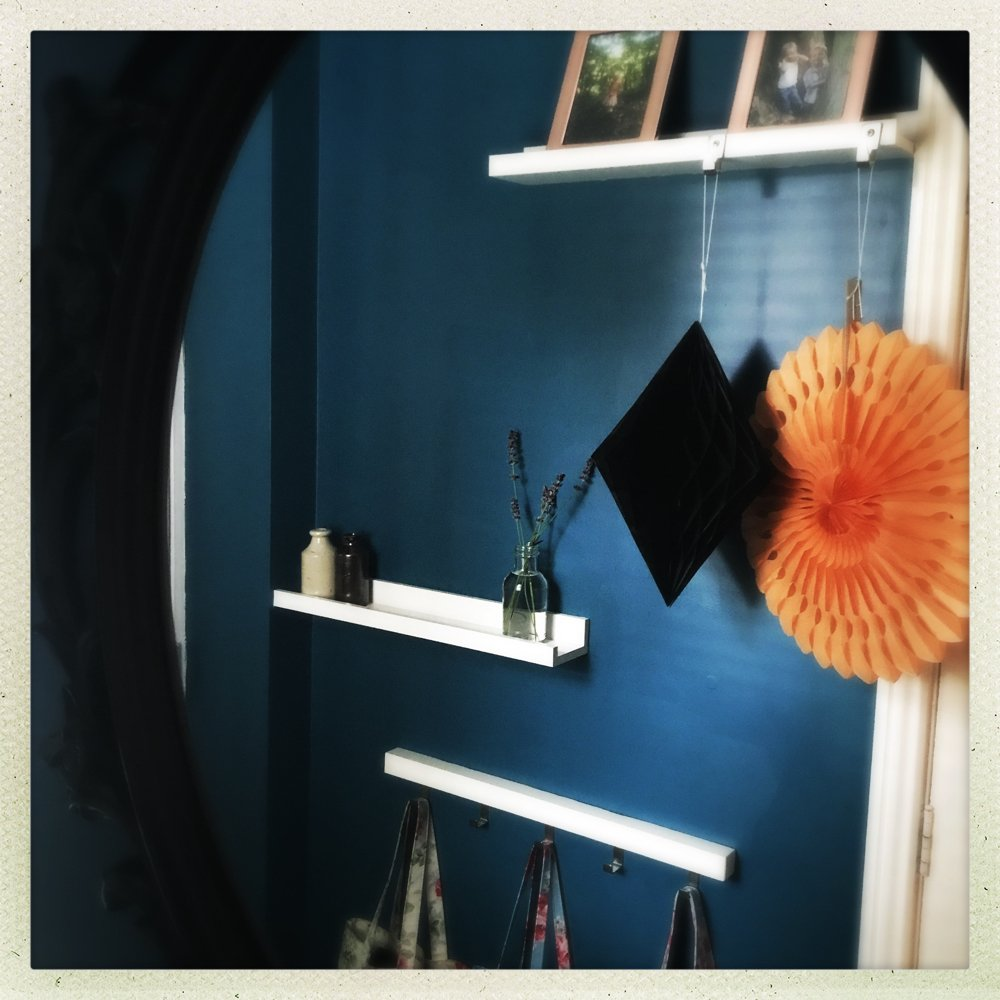 dark blue painted hallway with orange and black paper halloween decorations reflected in the mirror