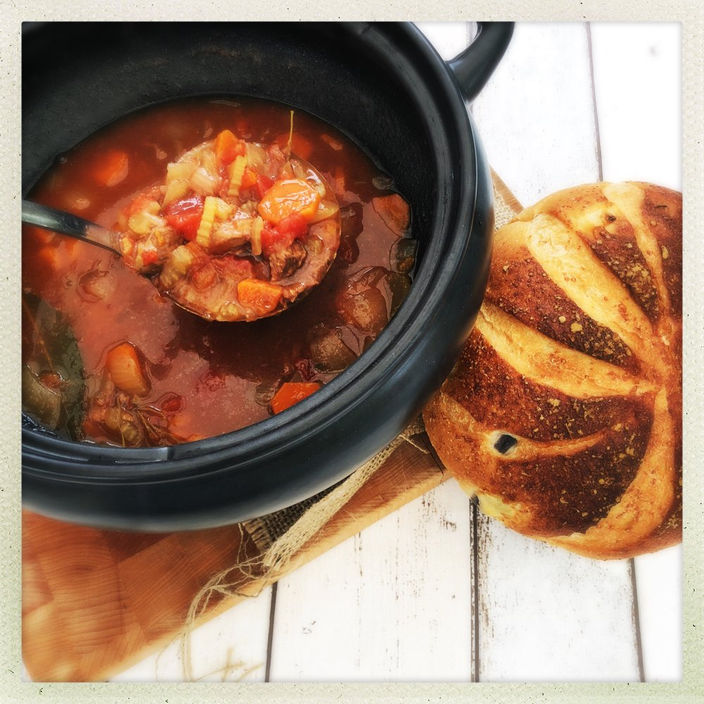 crock pot filled with homemade beef and ale stew alongside an artisan cheese and onion loaf.
