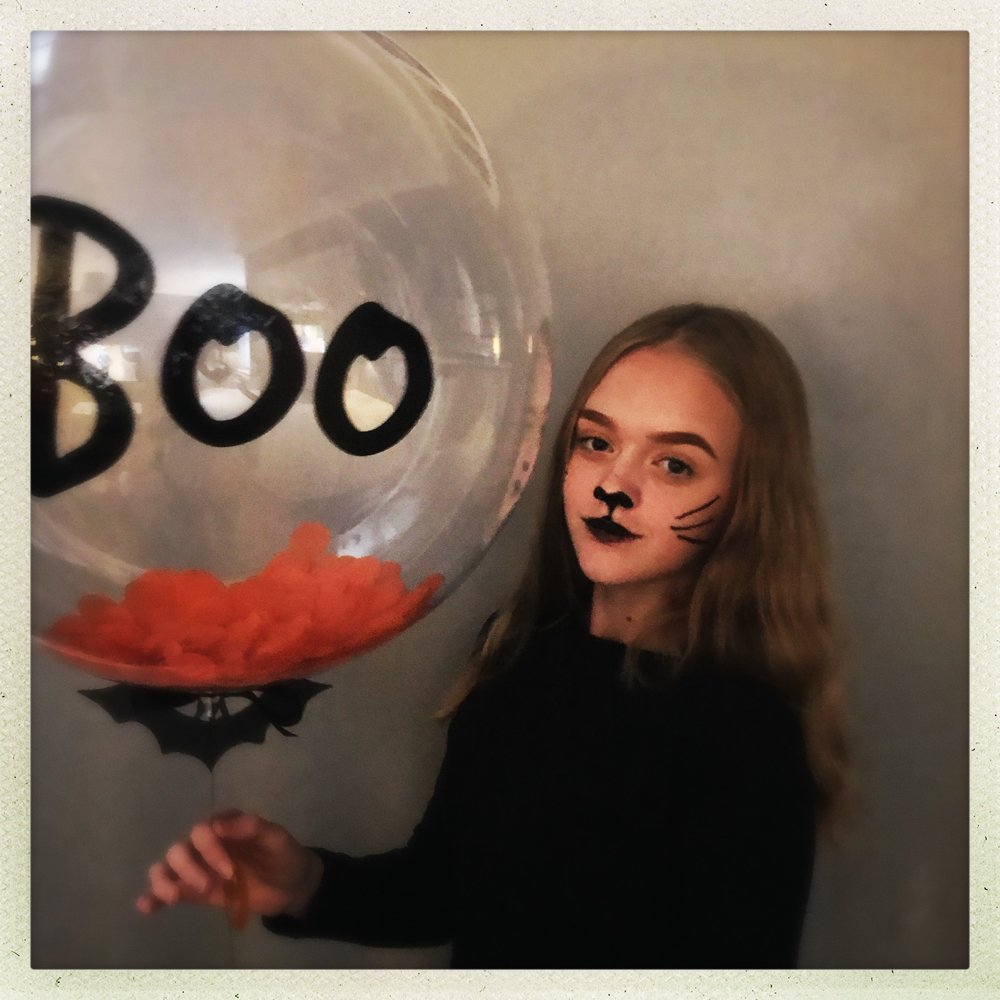 blonde girl dressed in black with cat face paint holding a Boo Halloween ballon