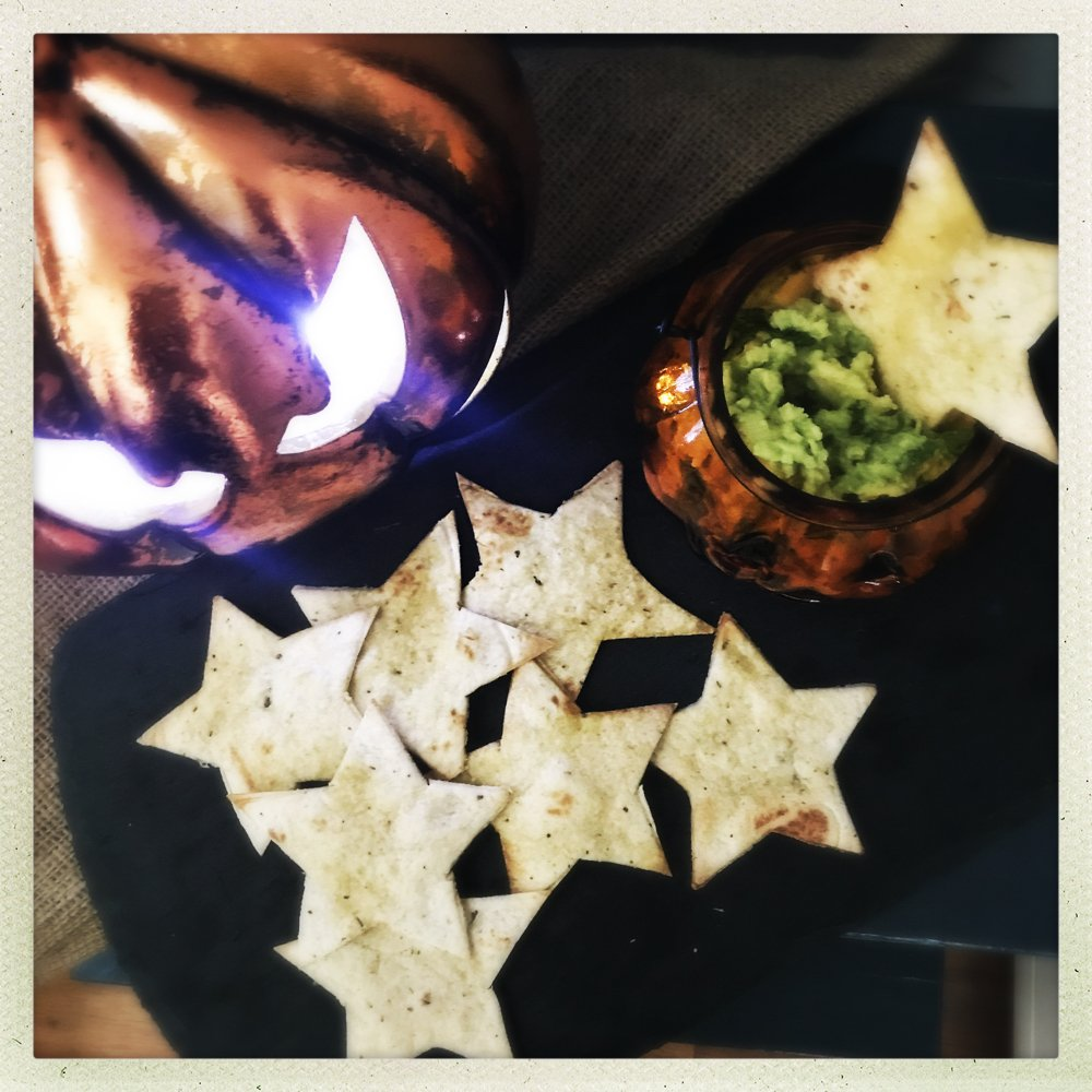 homemade slime dip with tortilla stars served in a pumpkin jack o lantern bowl.
