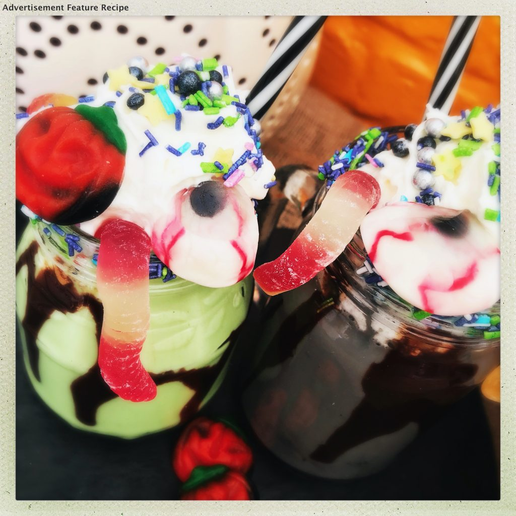 halloween milkshakes - green and black milkshakes in kilner jars topped with whipped cream, halloween sprinkles, jelly sweets and jelly worms.