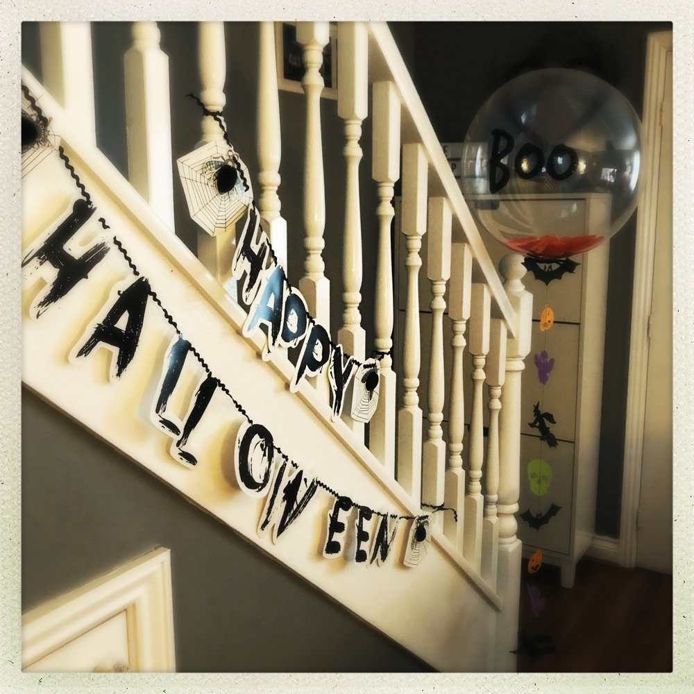 black and white happy halloween banner strung from the stair spindles with huge Halloween boo balloon