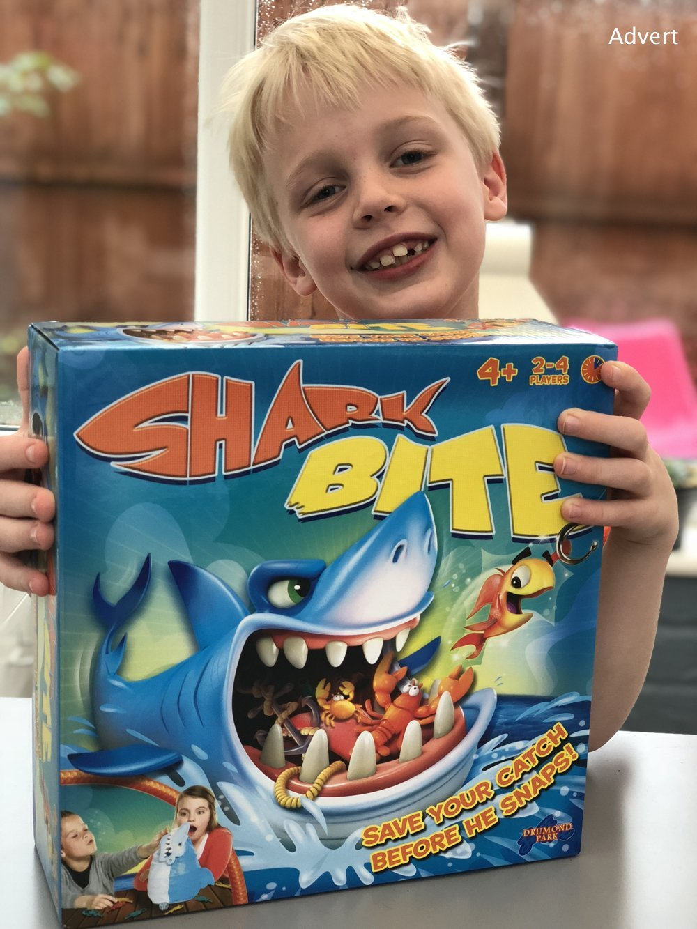 blonde boy holding Shark Bite game smiling