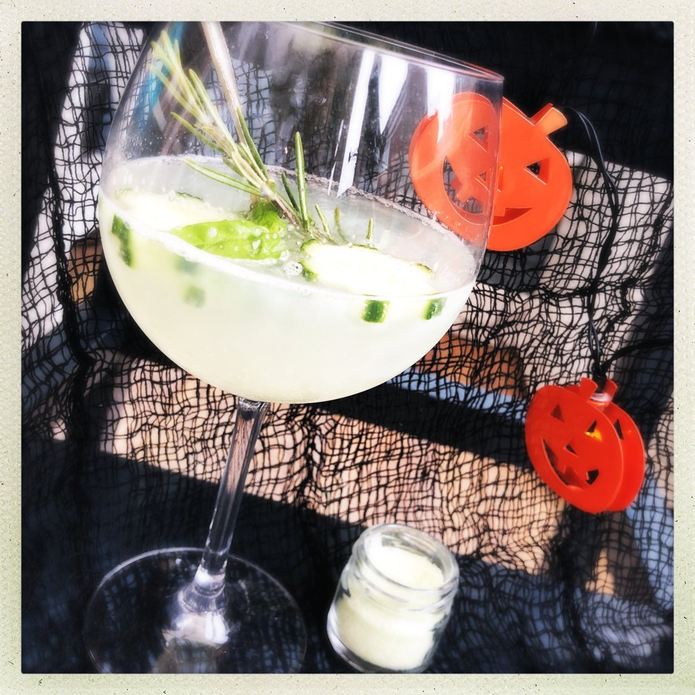 Halloween green sparkly gin and tonic served with rosemary and basil - surrounded by mini orange pumpkin lights
