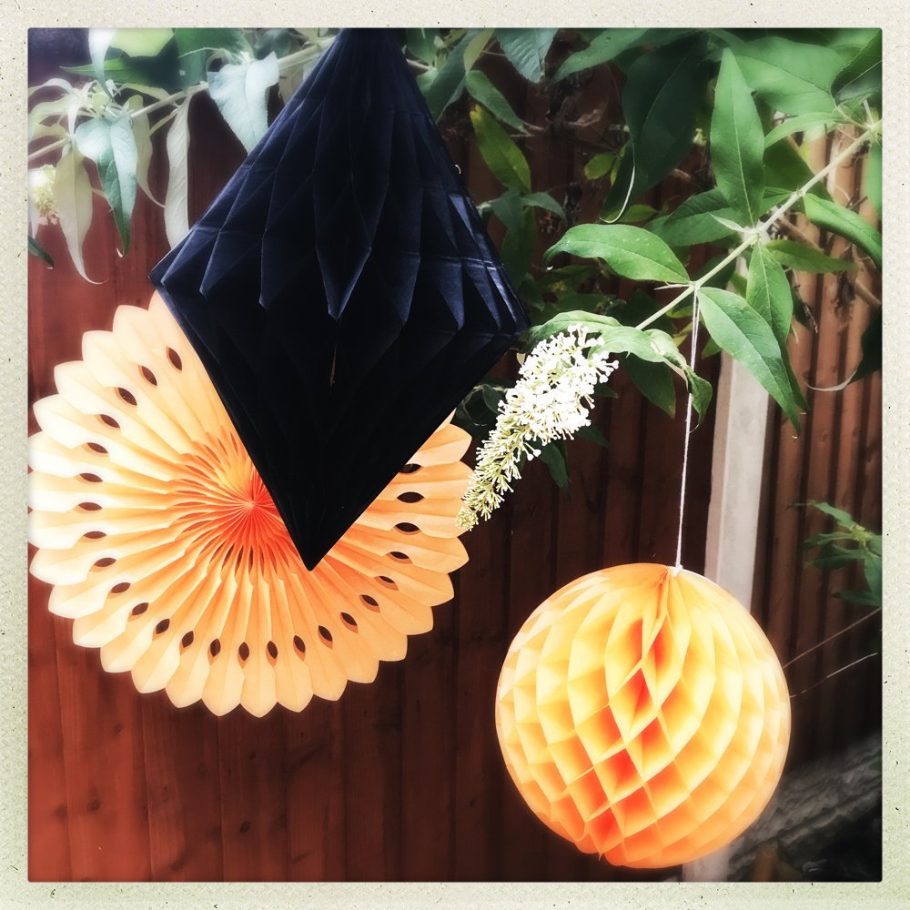orange and black paper Halloween decorations hung in the trees in the garden