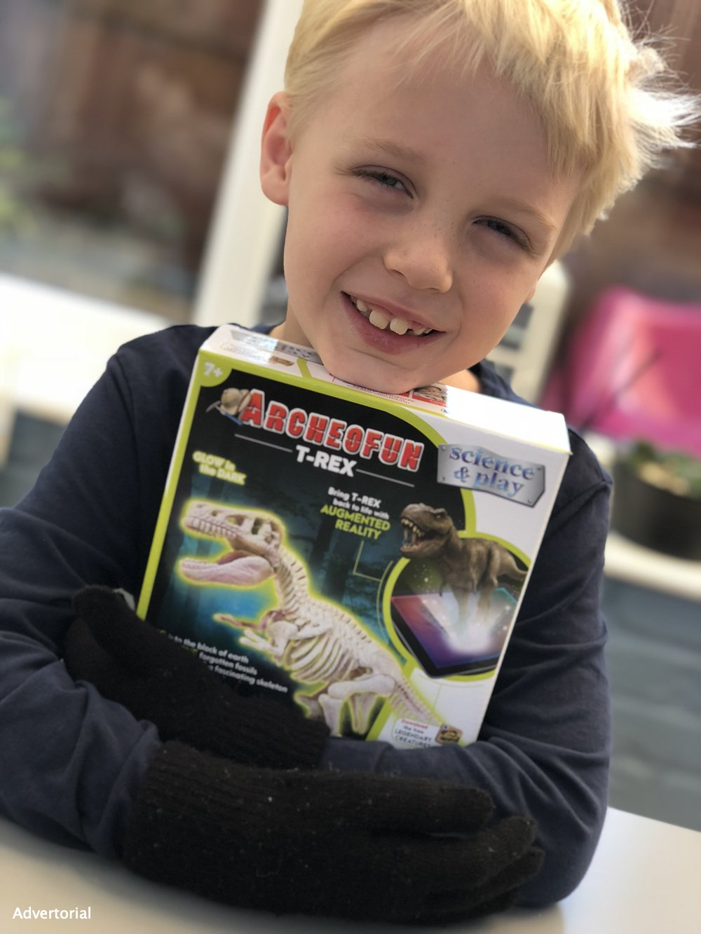 boy holding a Archeofun glow in the dark t-rex archeology kit