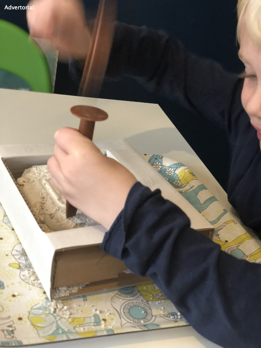 boy using play chisel to dig out archeofun dinosaur fossils