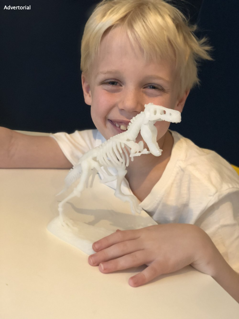 boy holding up a glow in the dark t-rex dinosaur skeleton from the archeofun science play kit