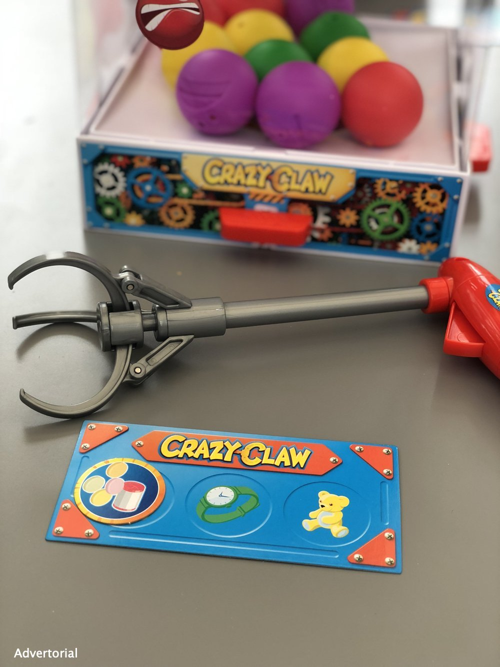 Crazy Claw game set up ready to play with claw and game card in front of the box of balls