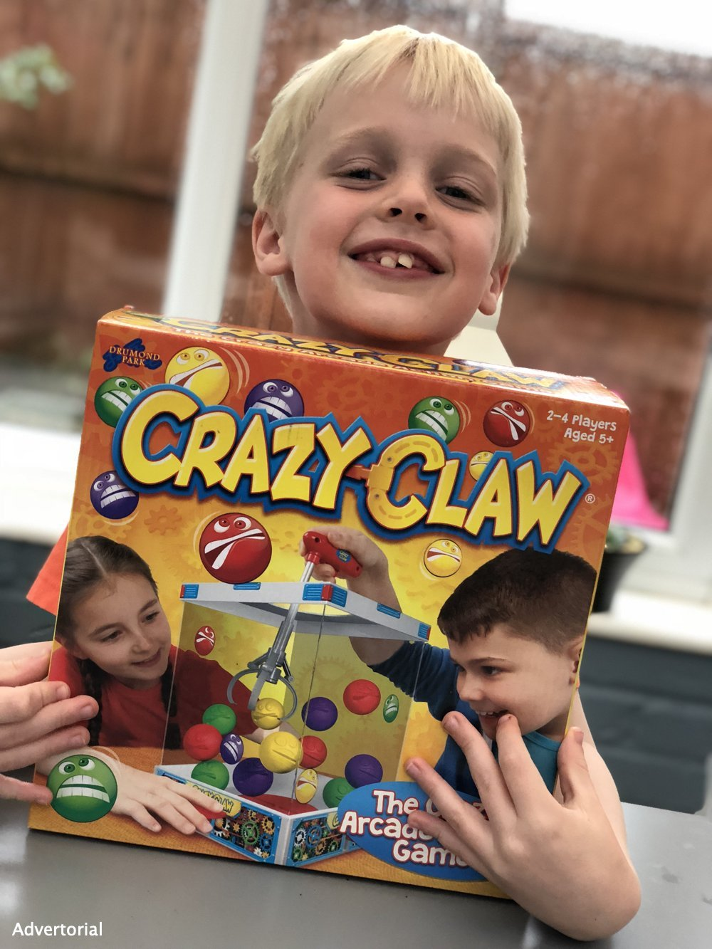 Boy holding the Crazy Claw game in the box