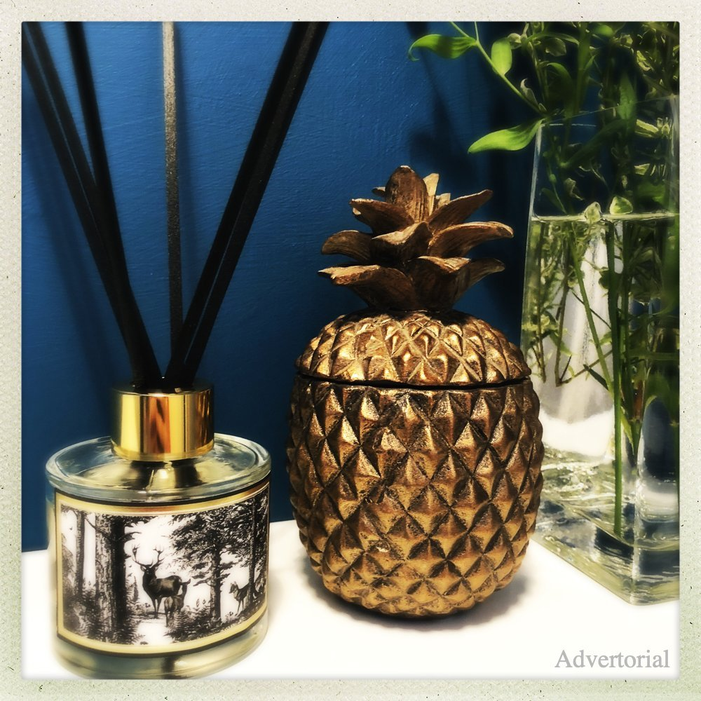 The Enchanted Forest reed diffuser stood by a bronze pineapple and vase of wildflowers against a dark blue painted wall
