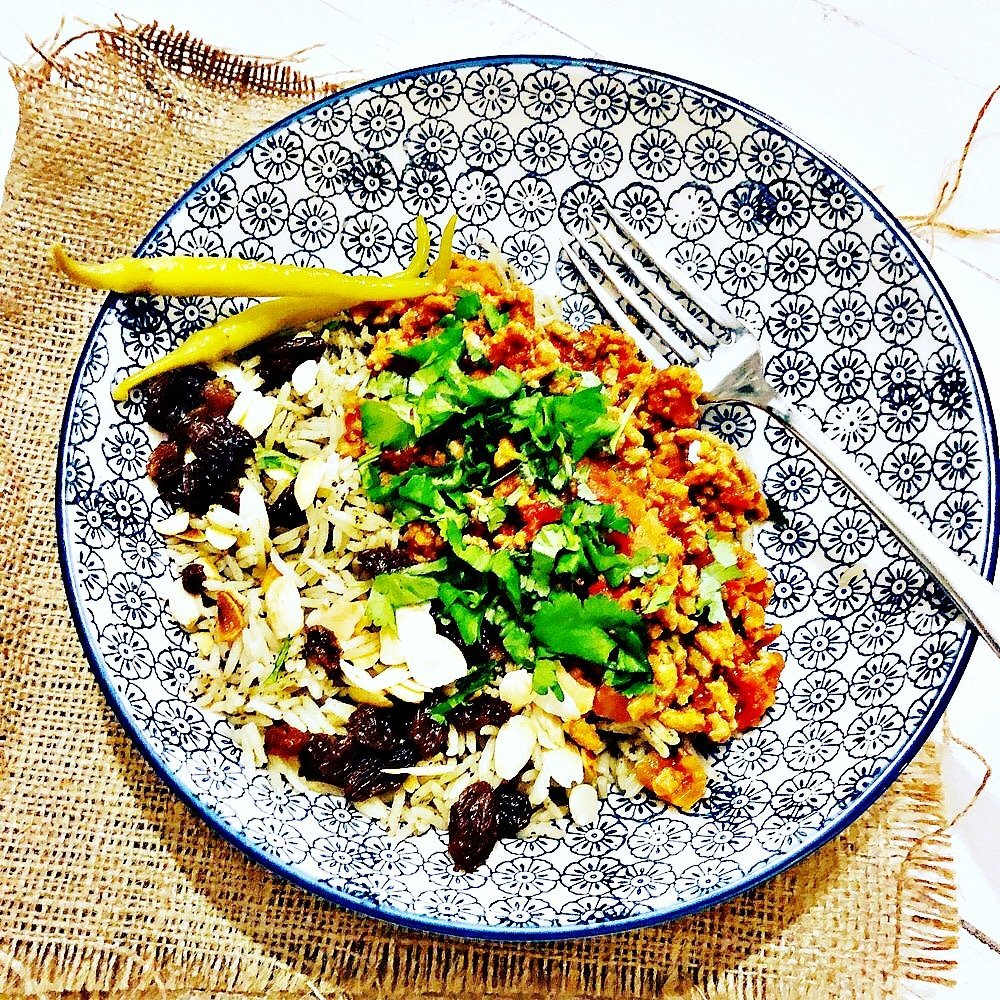 moroccan lamb mince with rice, scattered over are sultanas and flaked almonds, served with two chilli pickled chilli peppers.